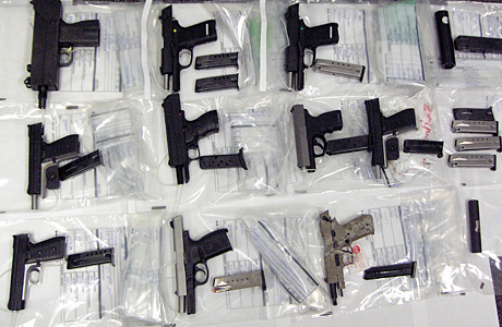 CBSA agents display guns seized at the Coutts border crossing. Photograph by: Handout, Courtesy CBSA
